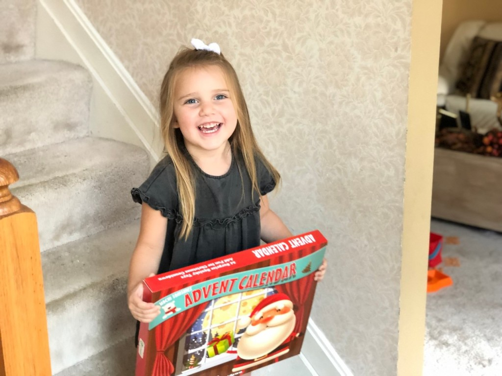 little girl with big smile holding advent calendar