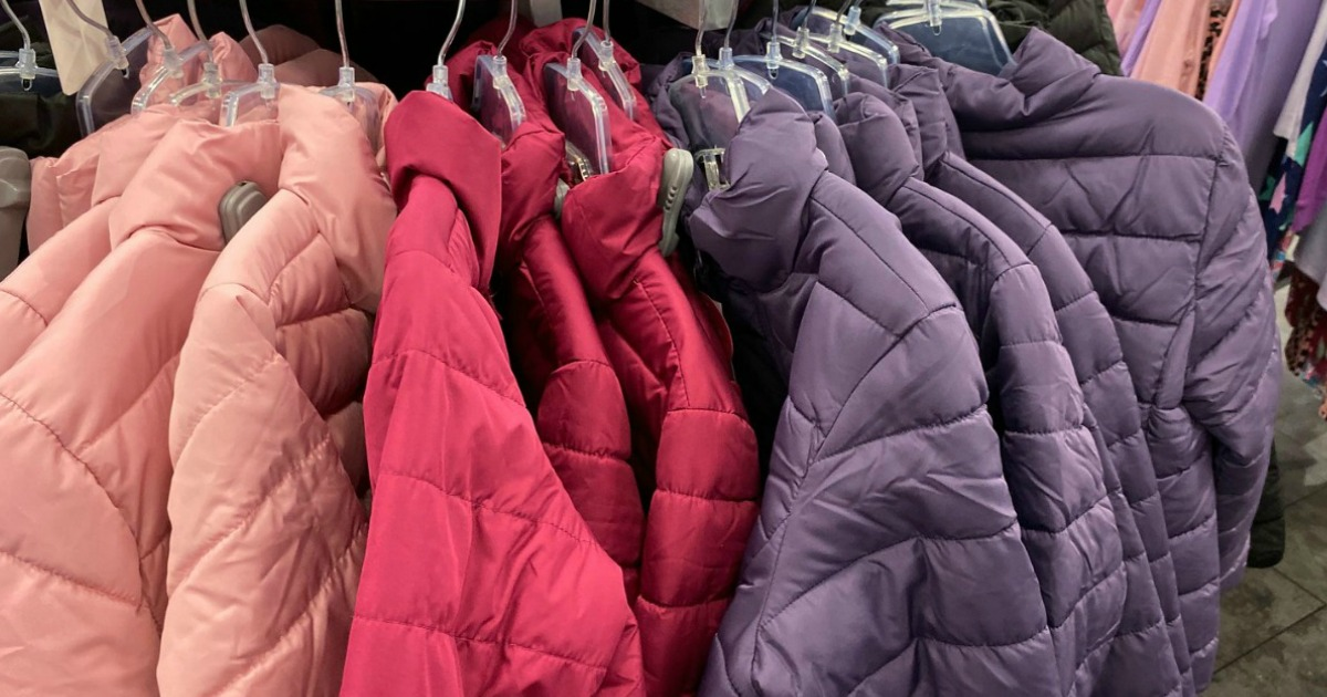 girls pastel colored puffer coats on store rack