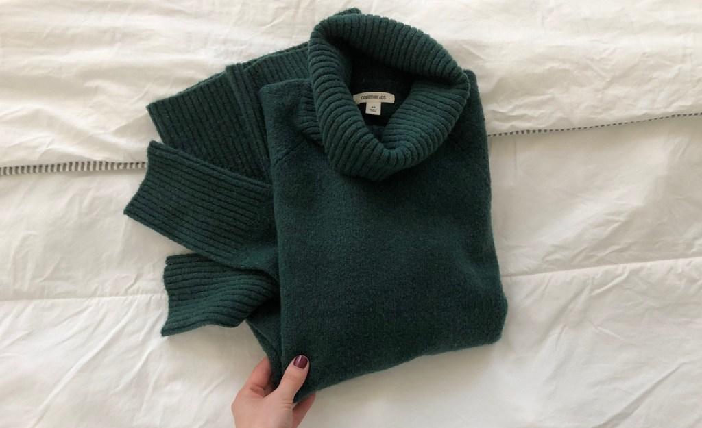 hand holding emerald green sweater