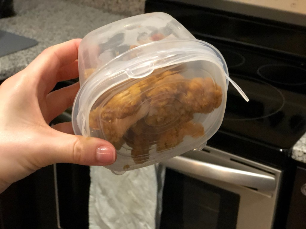 holding tupperware container with leftovers inside and silicone stretch lid on top