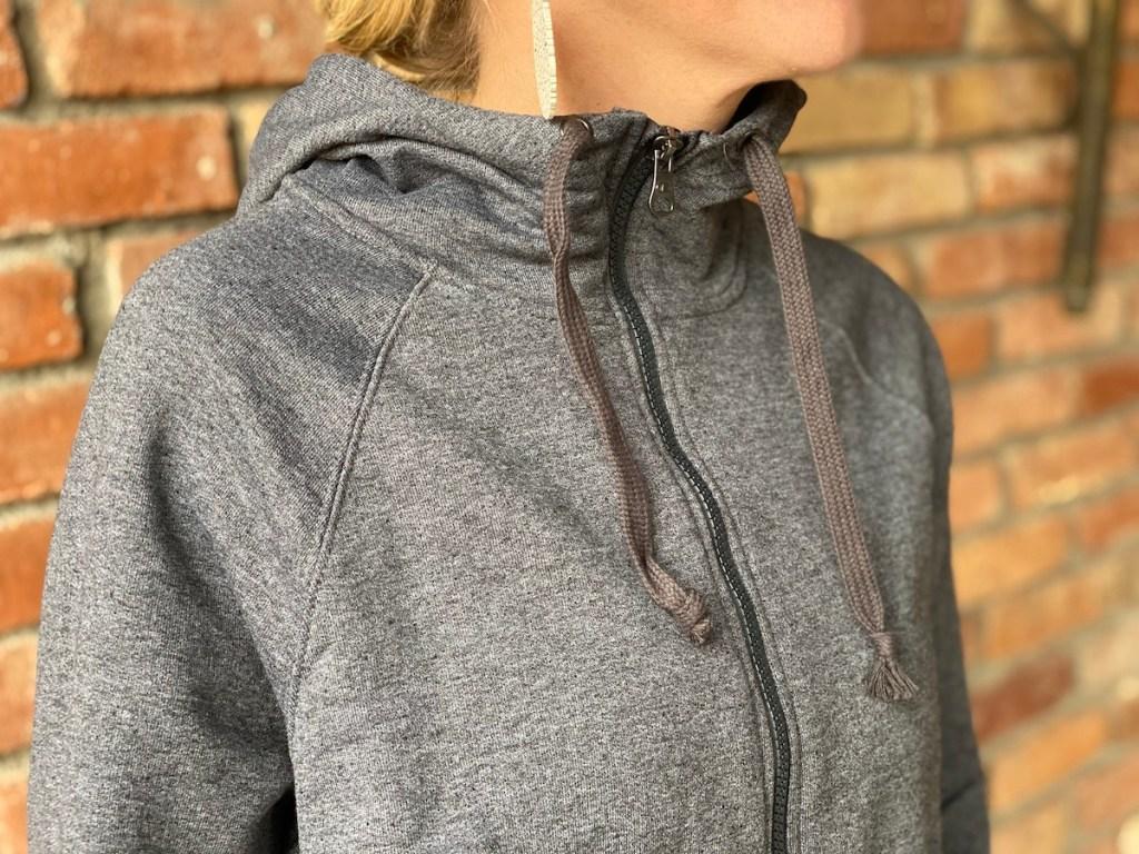woman wearing gray hoodie against brick wall