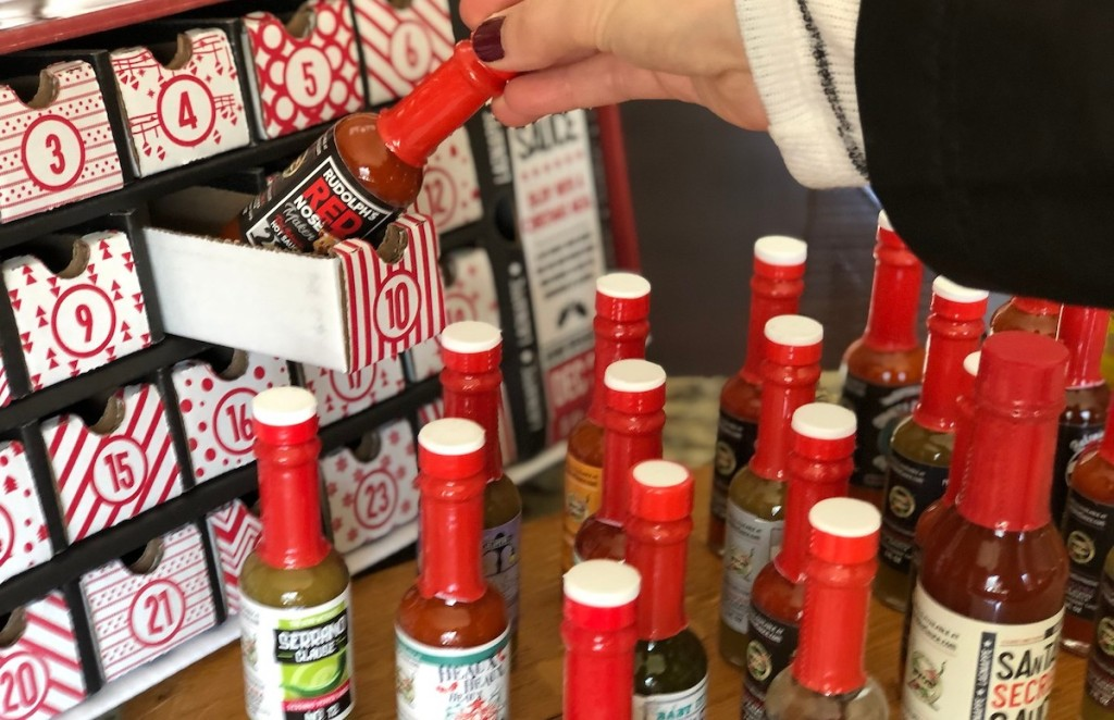 hand taking out box of hot sauces from advent calendar