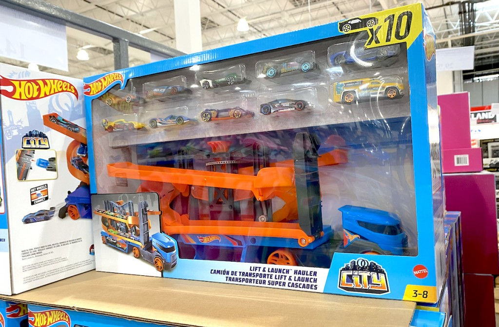 hot wheels truck with tons of cars in blue box stacked on store shelf
