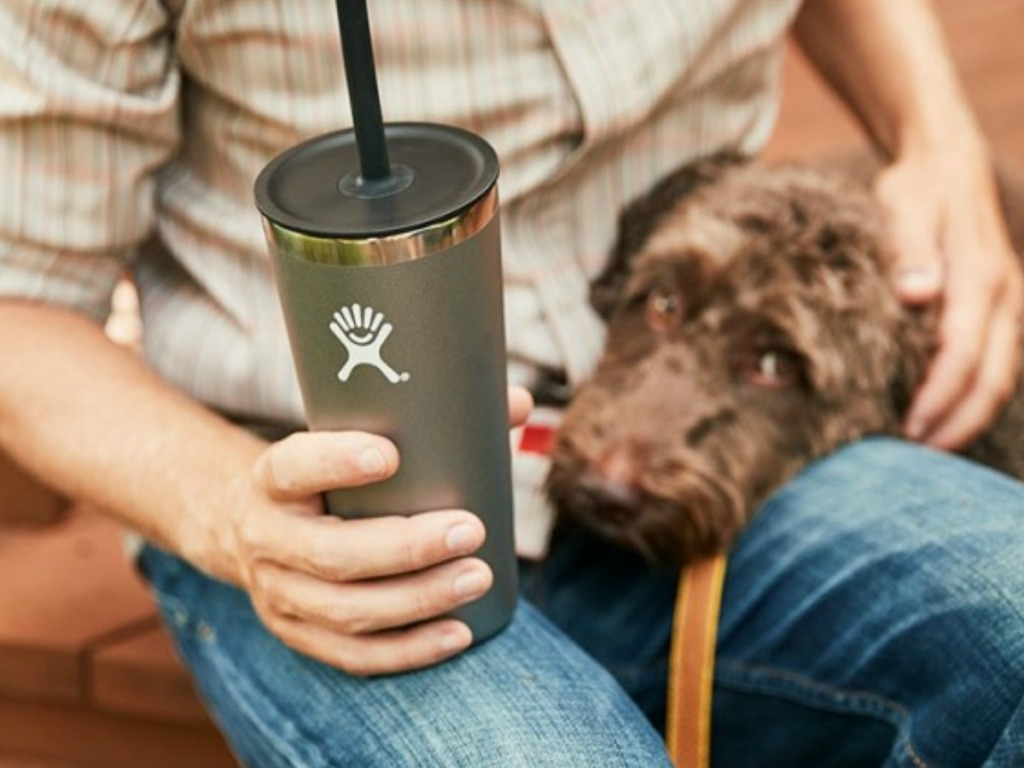 man holding cup with straw and dog on his lap