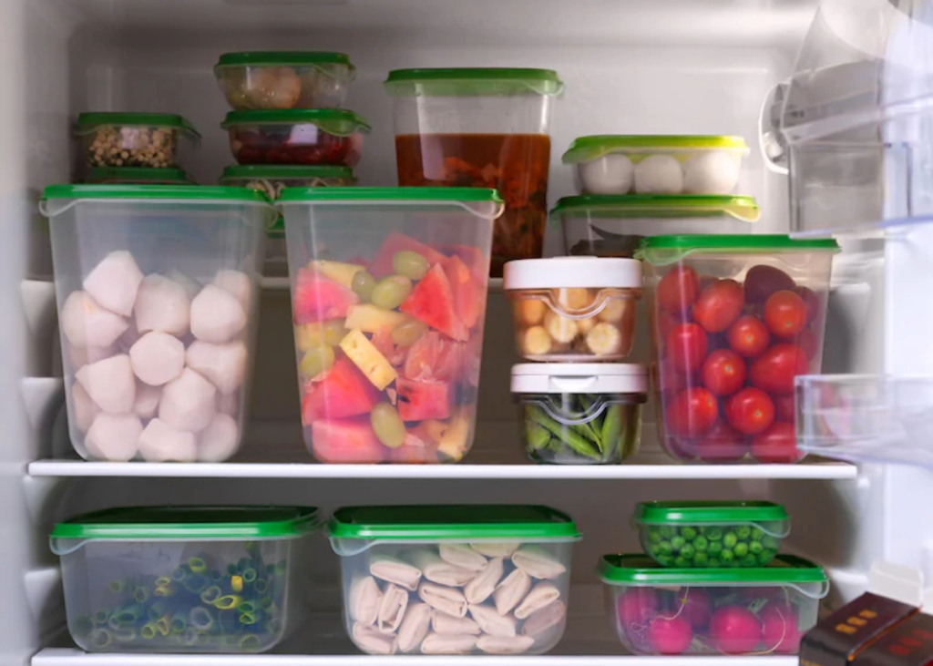 green and clear ikea food containers with food stacked in fridge
