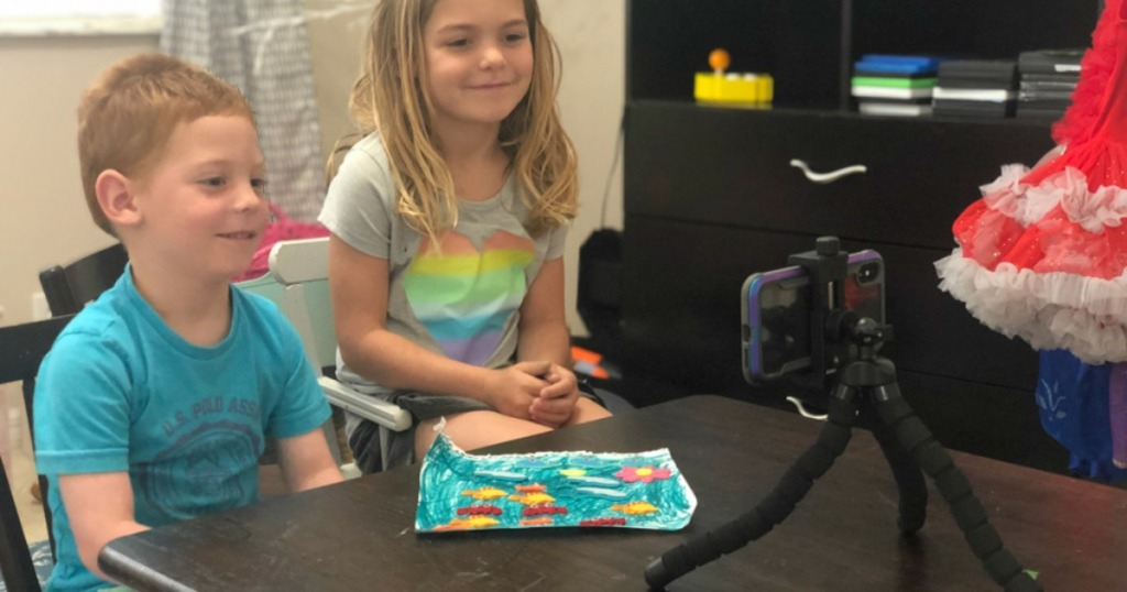 kids sitting at table looking at phone on tripod