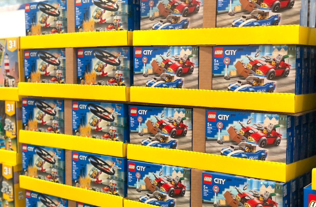 lego city vehicle sets stacked in rows on store shelf