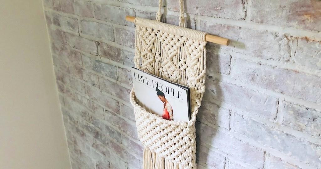 macrame magazine holder hanging on brick wall