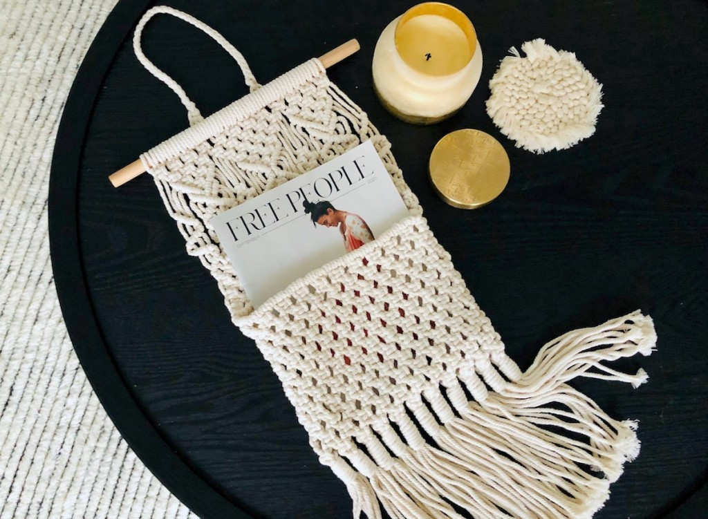 macrame hanger on black table with candle and magazine