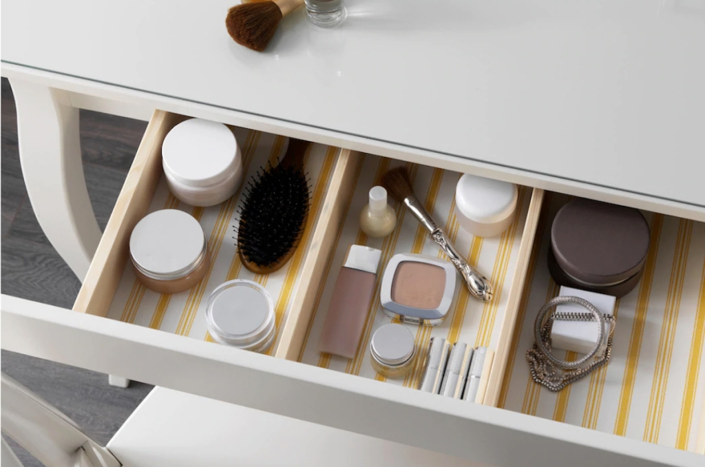 makeup drawer filled with brush and jars of stuff