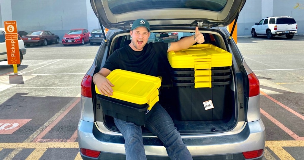 man in the back of car with yellow storage totes