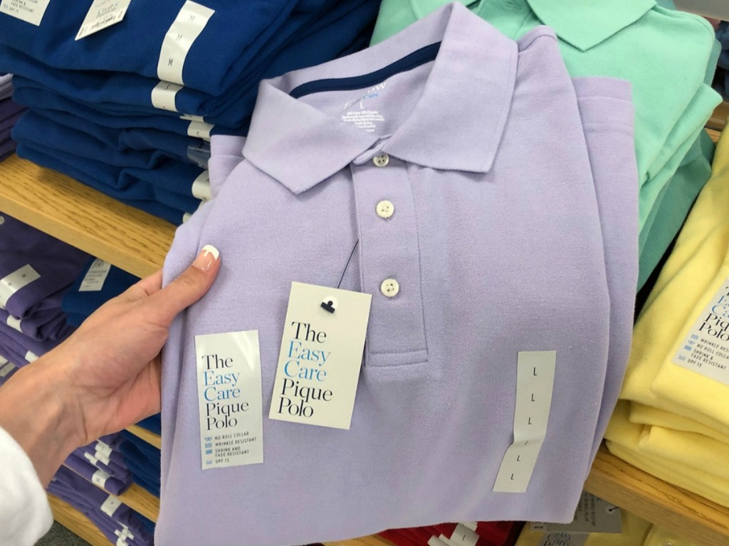 hand holding lavendar colored shirt by store display