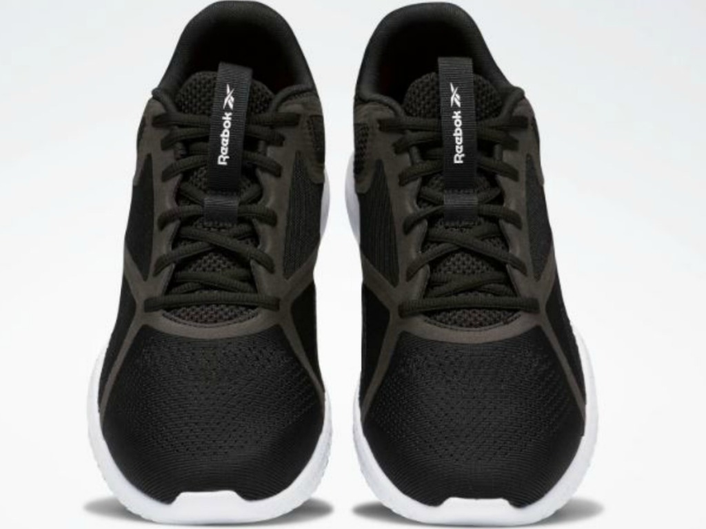 black pair of tennis shoes on white background