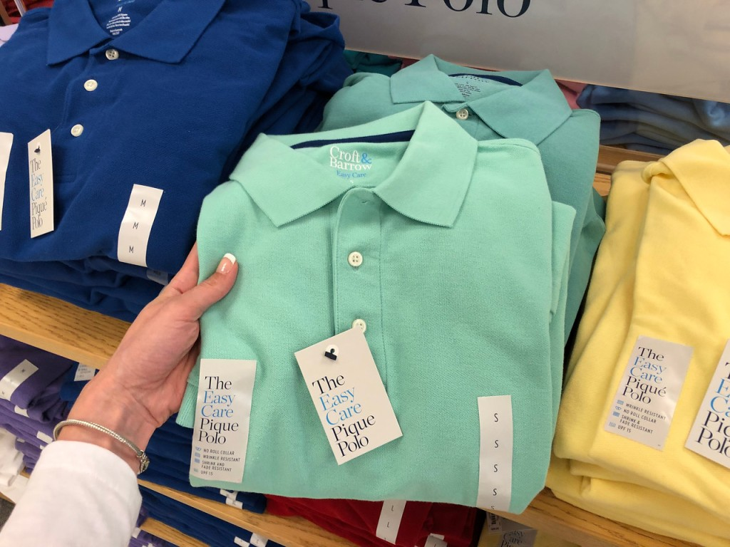 hand holding mint colored mans polo in store