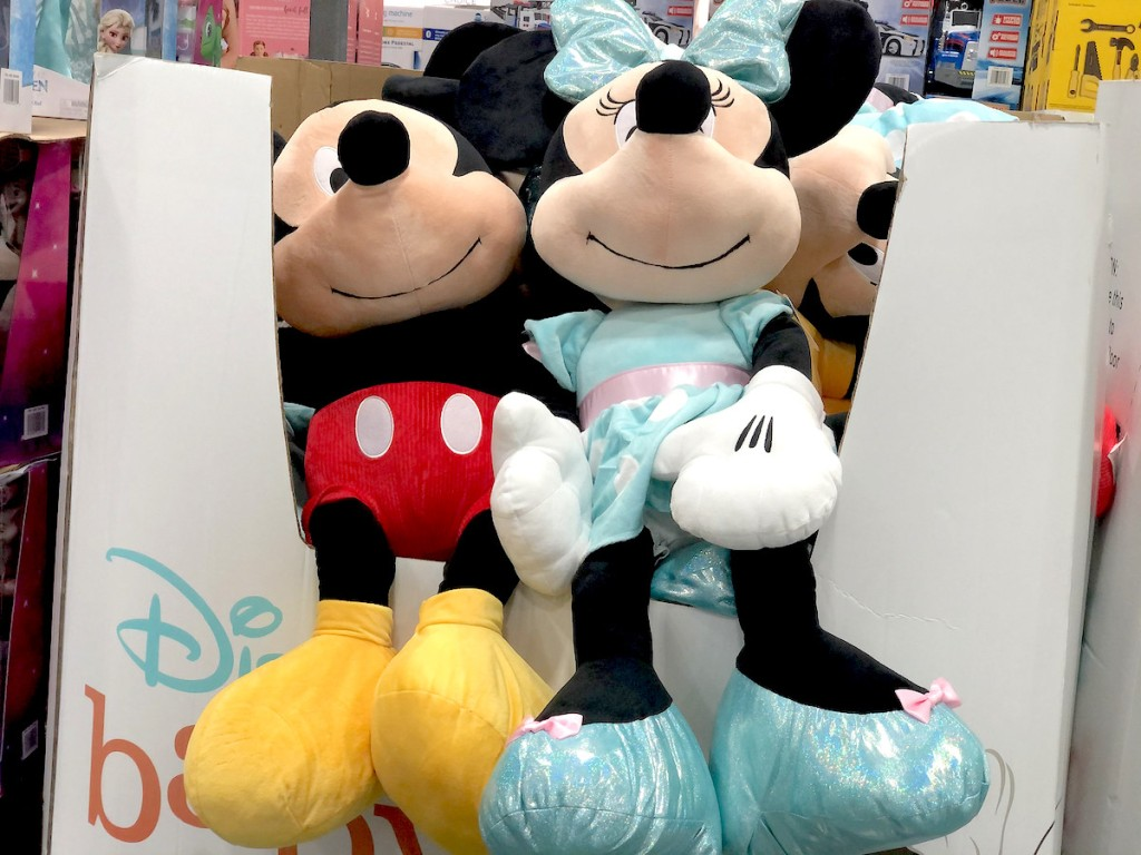 large jumpbo plush mickey and minnie mouse dolls sitting in cardboard box at store