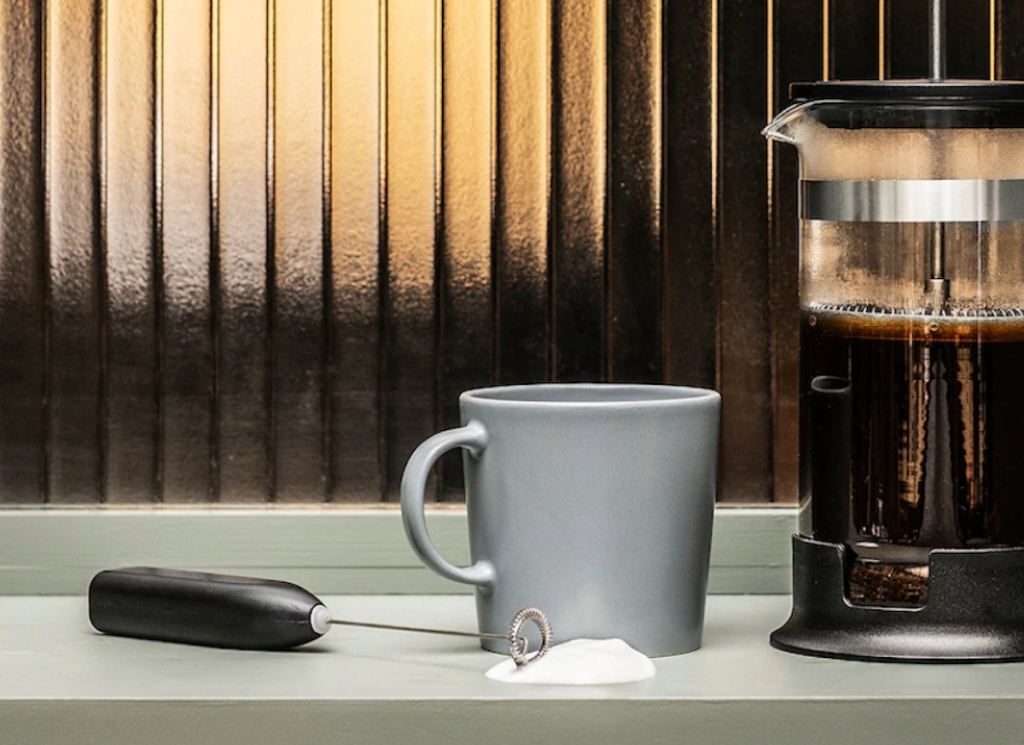 milk frother sitting on counter next to coffee mug and french press