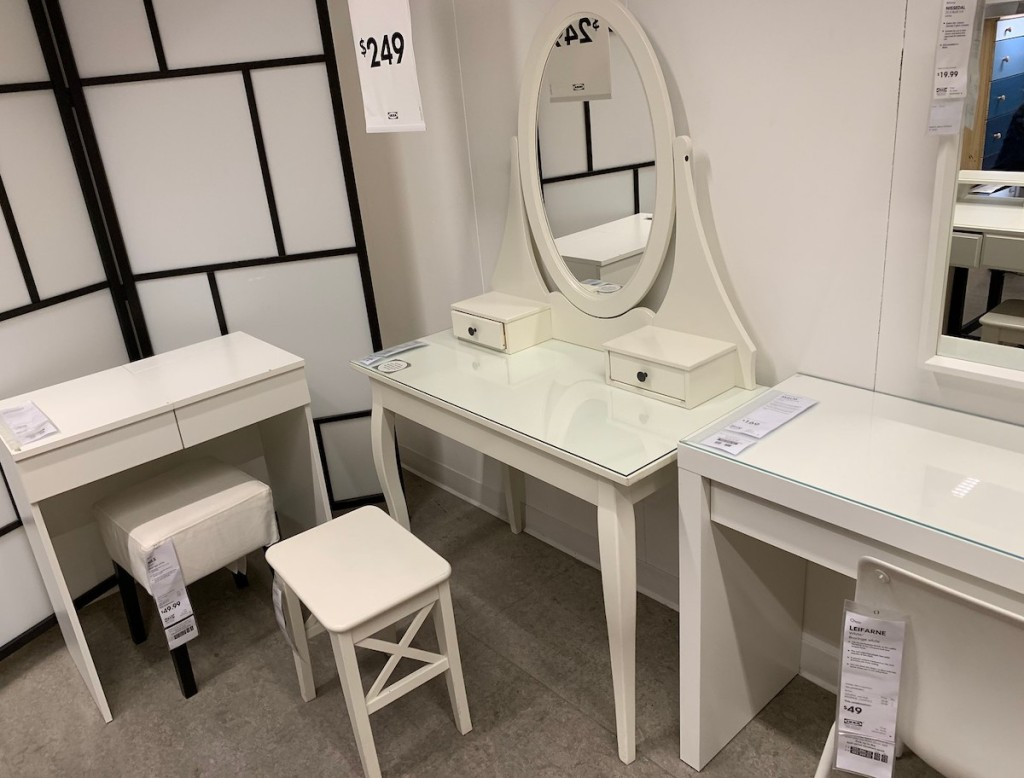 white vanity desk with oval mirror on top in ikea store