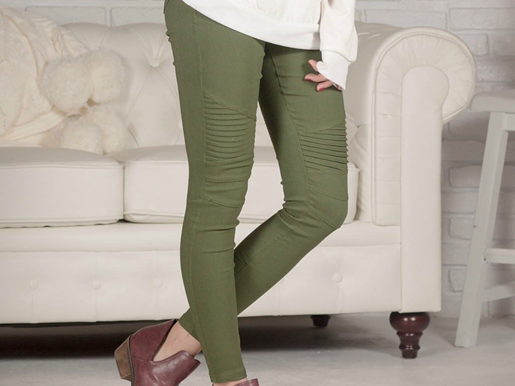 woman's legs with green pants in front of couch