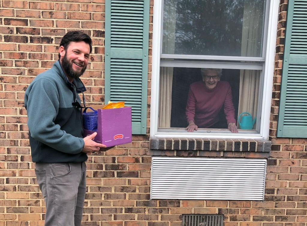 man holding a package in front of window with elder looking outside