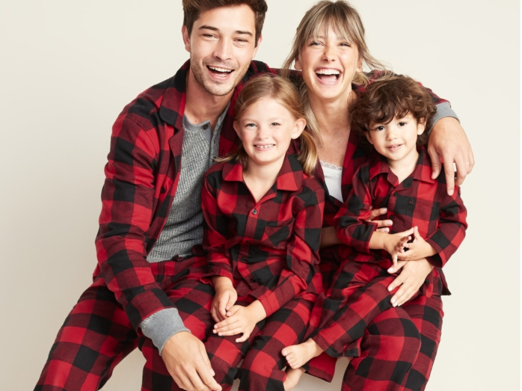 family all wearing black and red plaid flannel pajamas