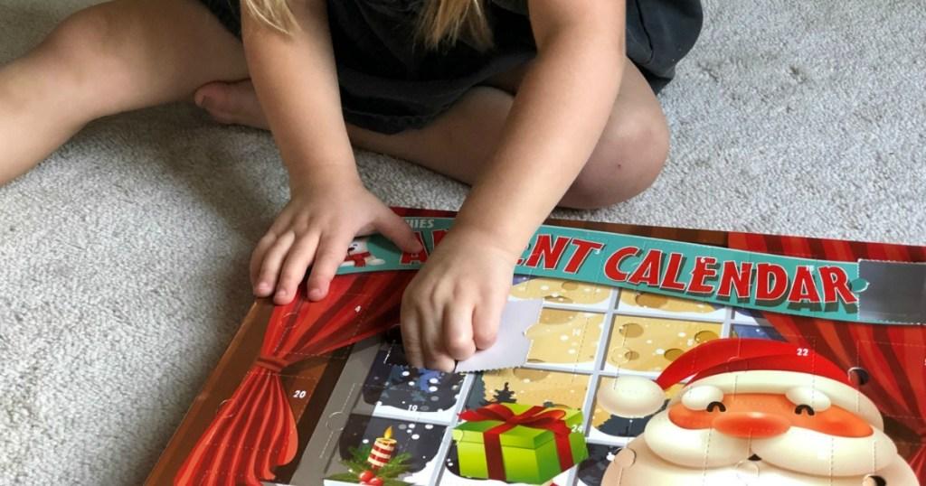 little girl opening Chritmas advent calendar