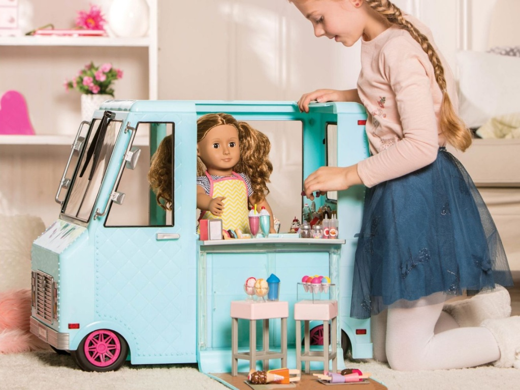 girl playing with ice cream truck and doll