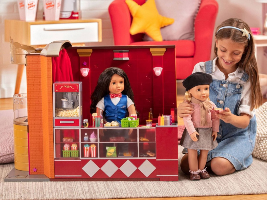 girl playing with movie set and dolls