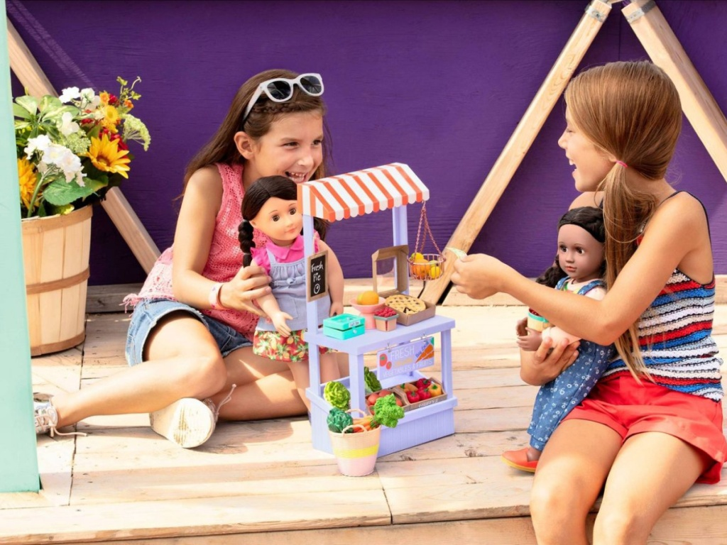 girls playing with farmers market set and dolls