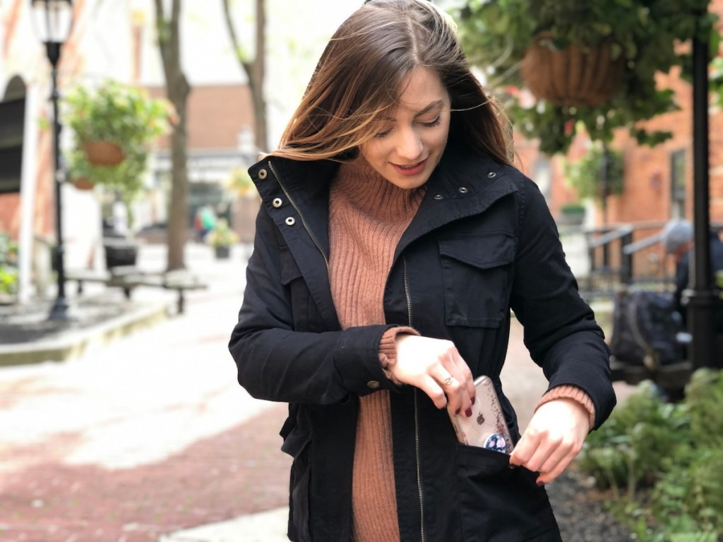 woman putting phone in cargo jacket pocket