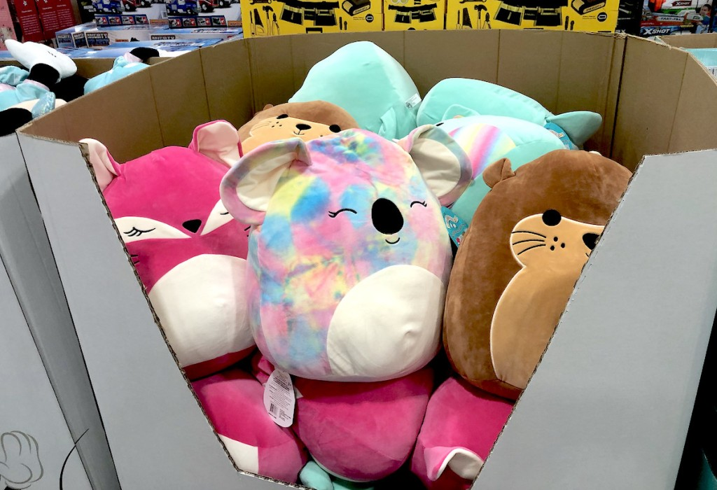 variety of colorful plush animals sitting in cardboard box at store