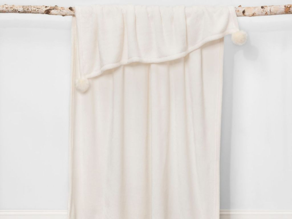 hanging white throw blanket with poms on each corner