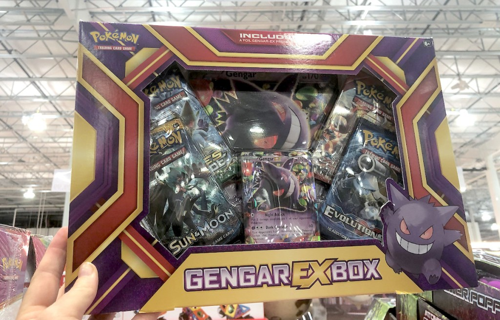 hand holding pokemon trading card game in store with bright lights