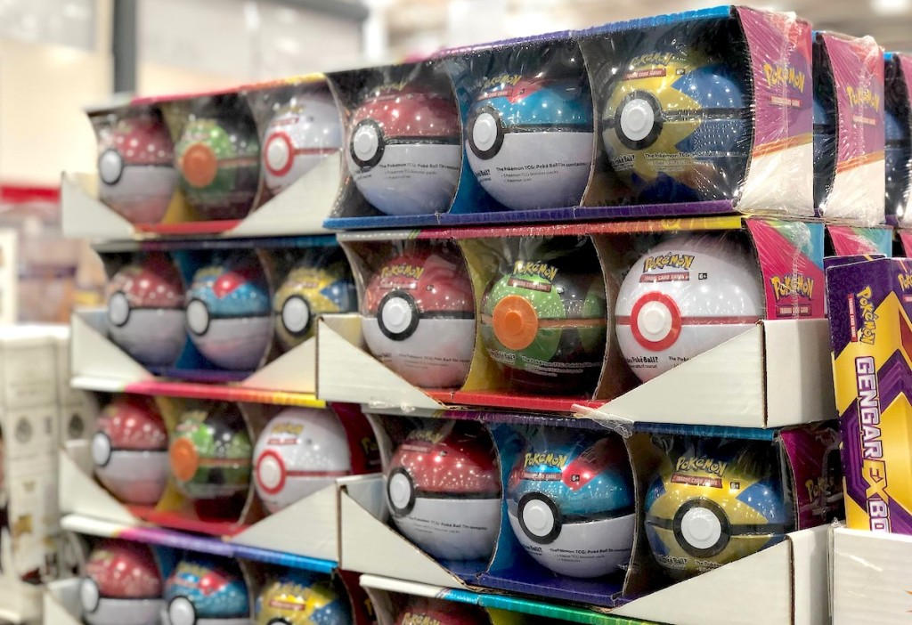 three packs of pokemon tin balls stacked in boxes in store
