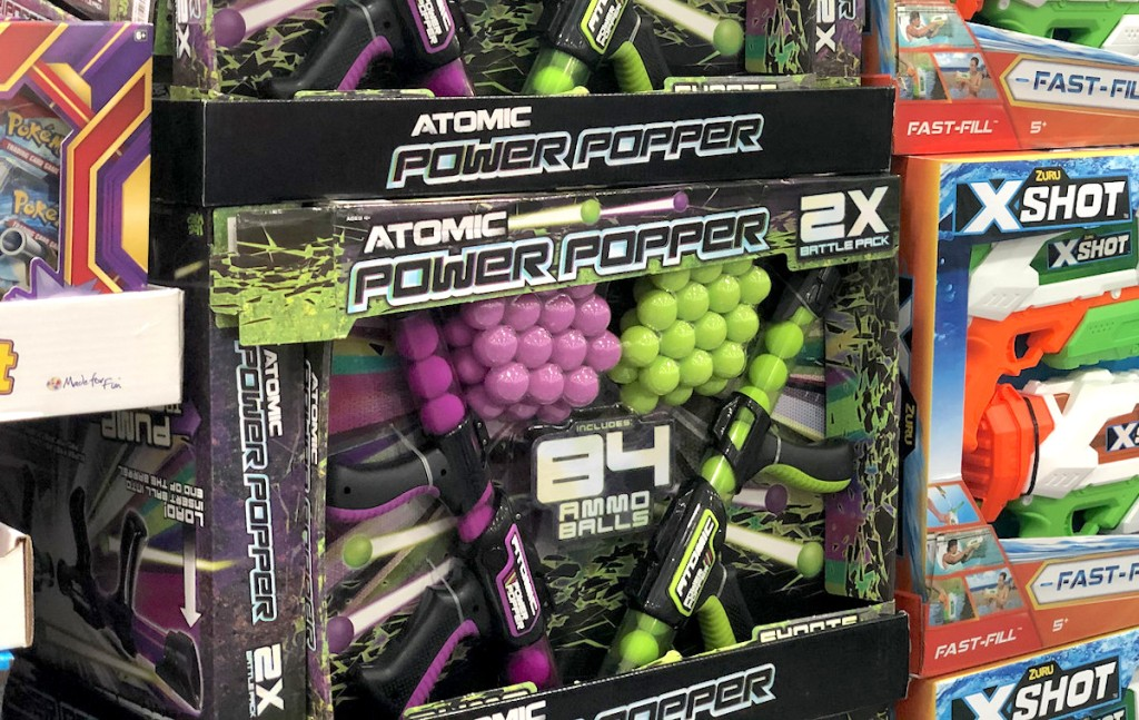 power popper purple and green toy stacked in boxes