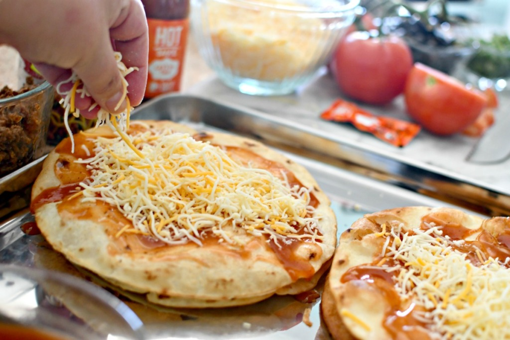 putting cheese on homemade pizzas