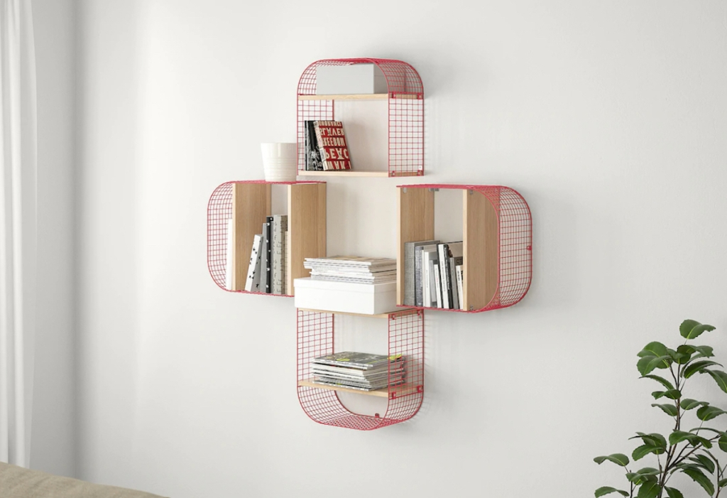 four red wire shelves on wall with books