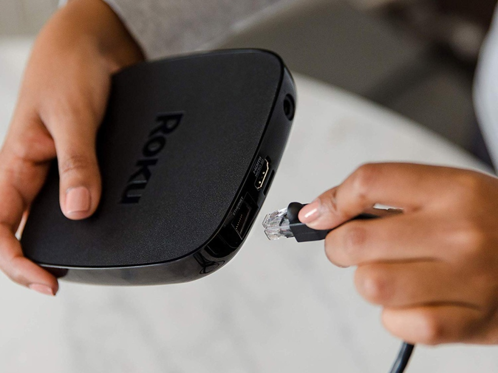 person plugging in a Roku Ultra
