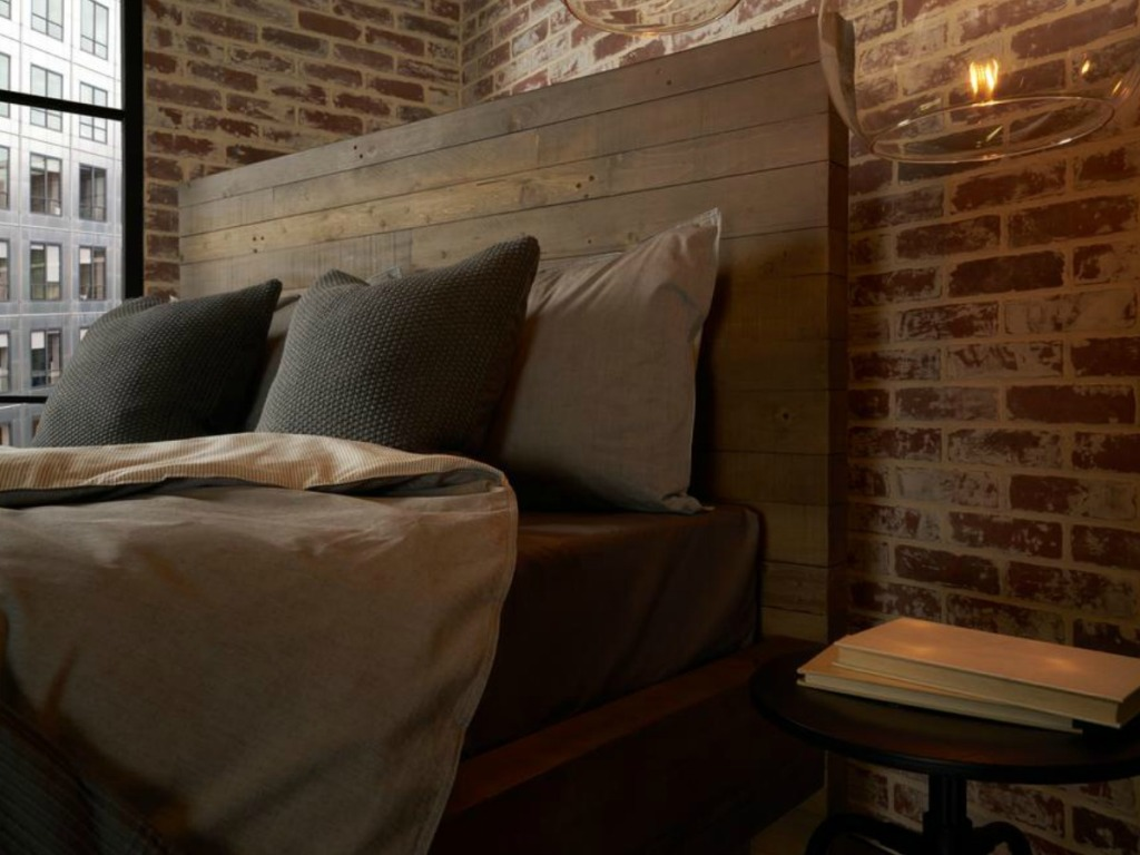 bed with blankets & sheets next to brick wall