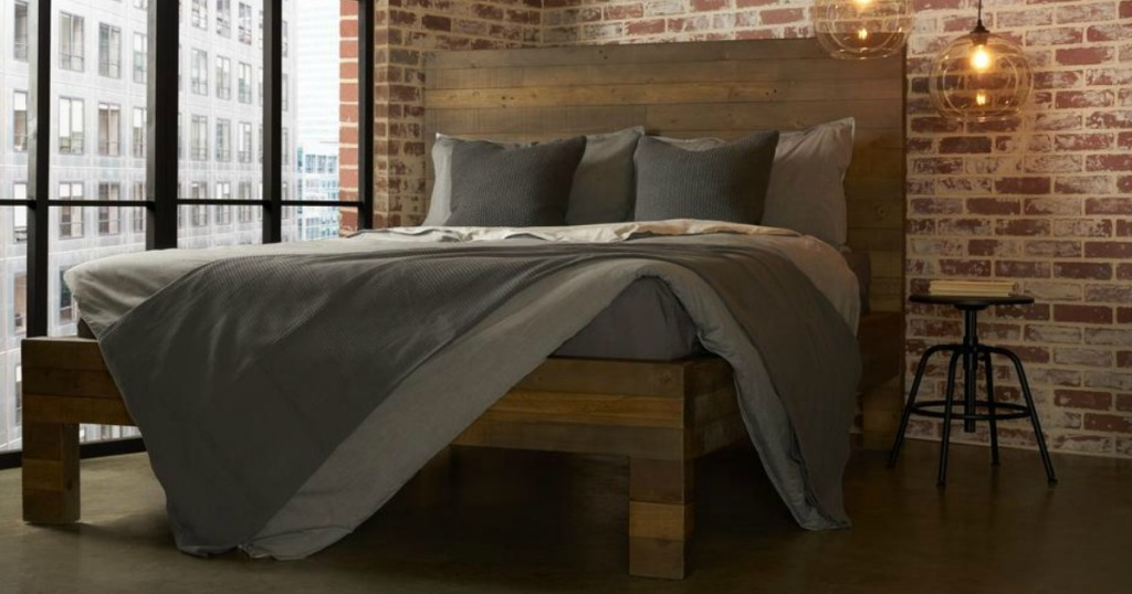 bed made with dark wood with grey covering