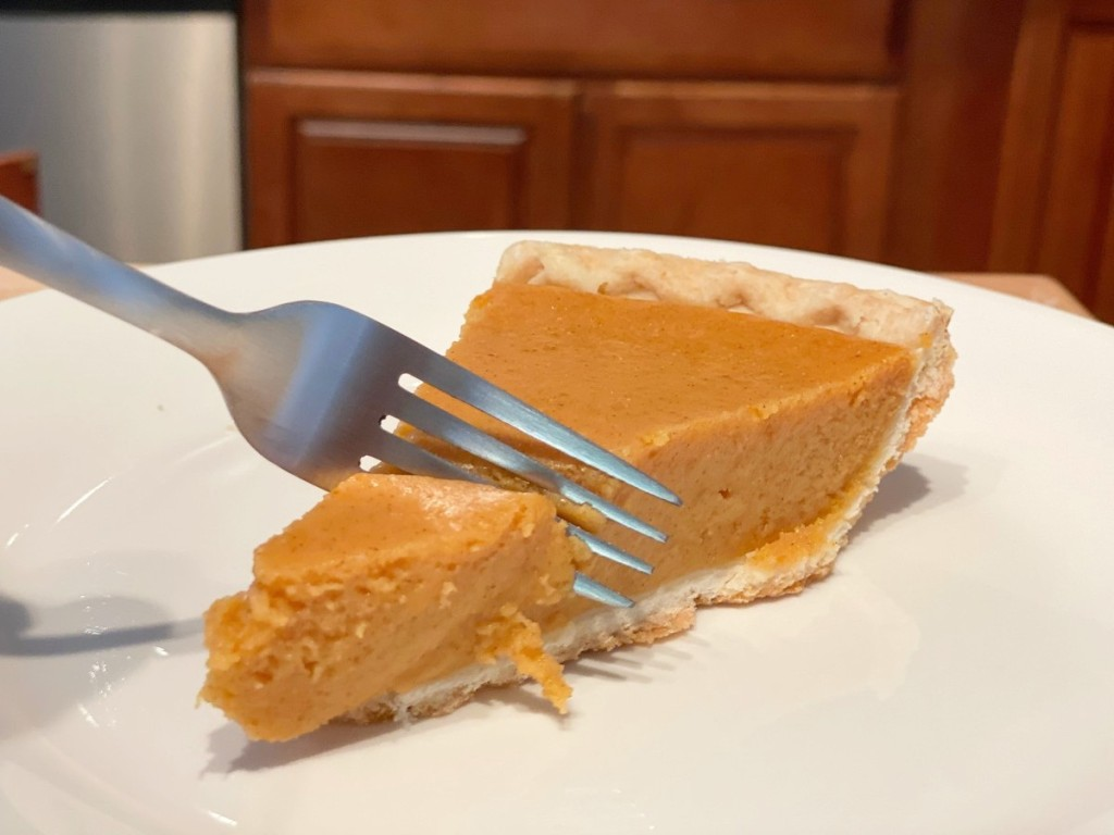 cutting a bite of pumpkin pie with a fork