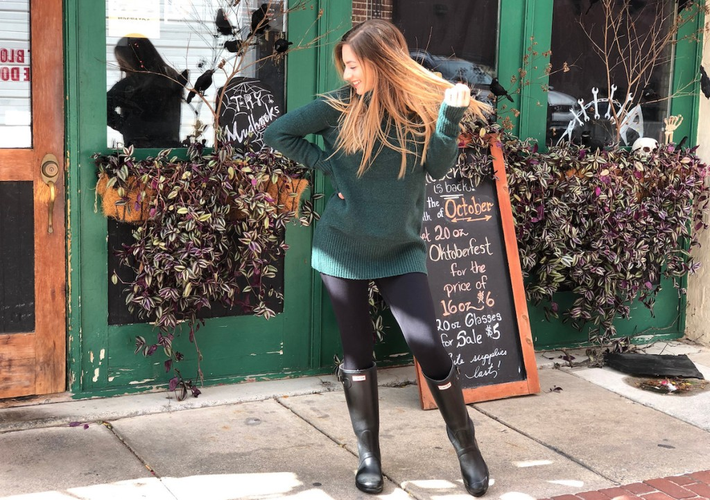 woman laughing wearing green amazon sweater and black leggings hunter boots