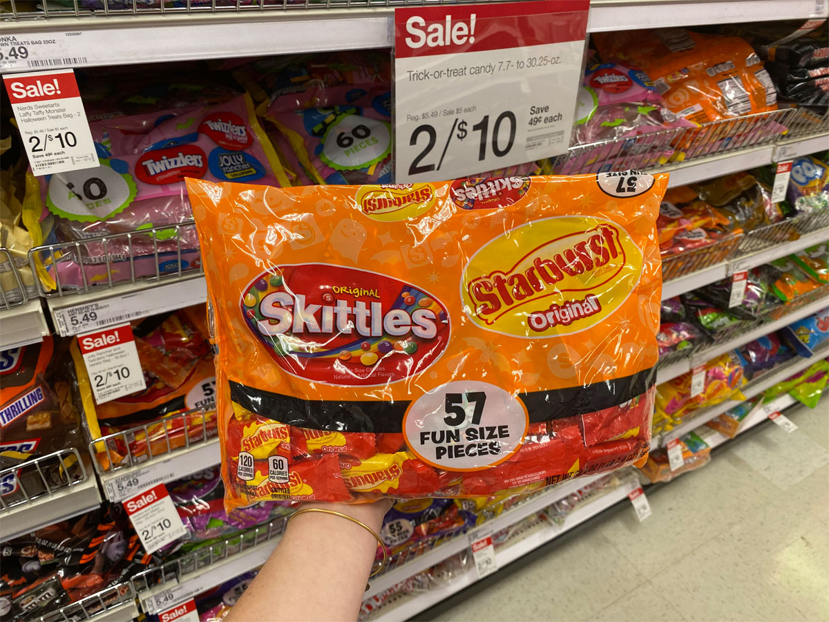 hand holding bag of skittle and starburst halloween fun size candy