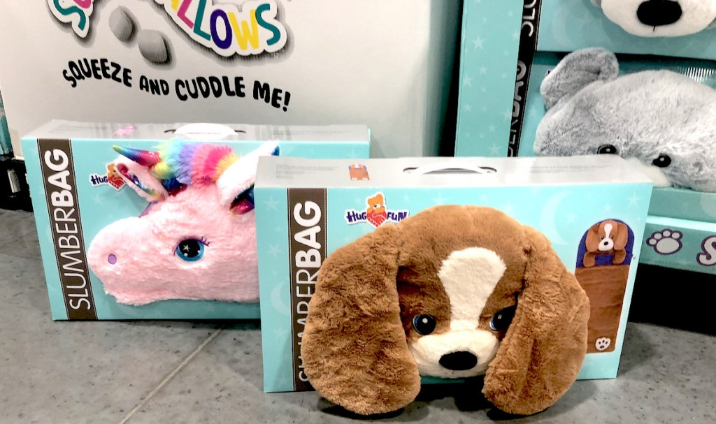 plush unicorn and puppy slumber bags in blue boxes sitting on store floor