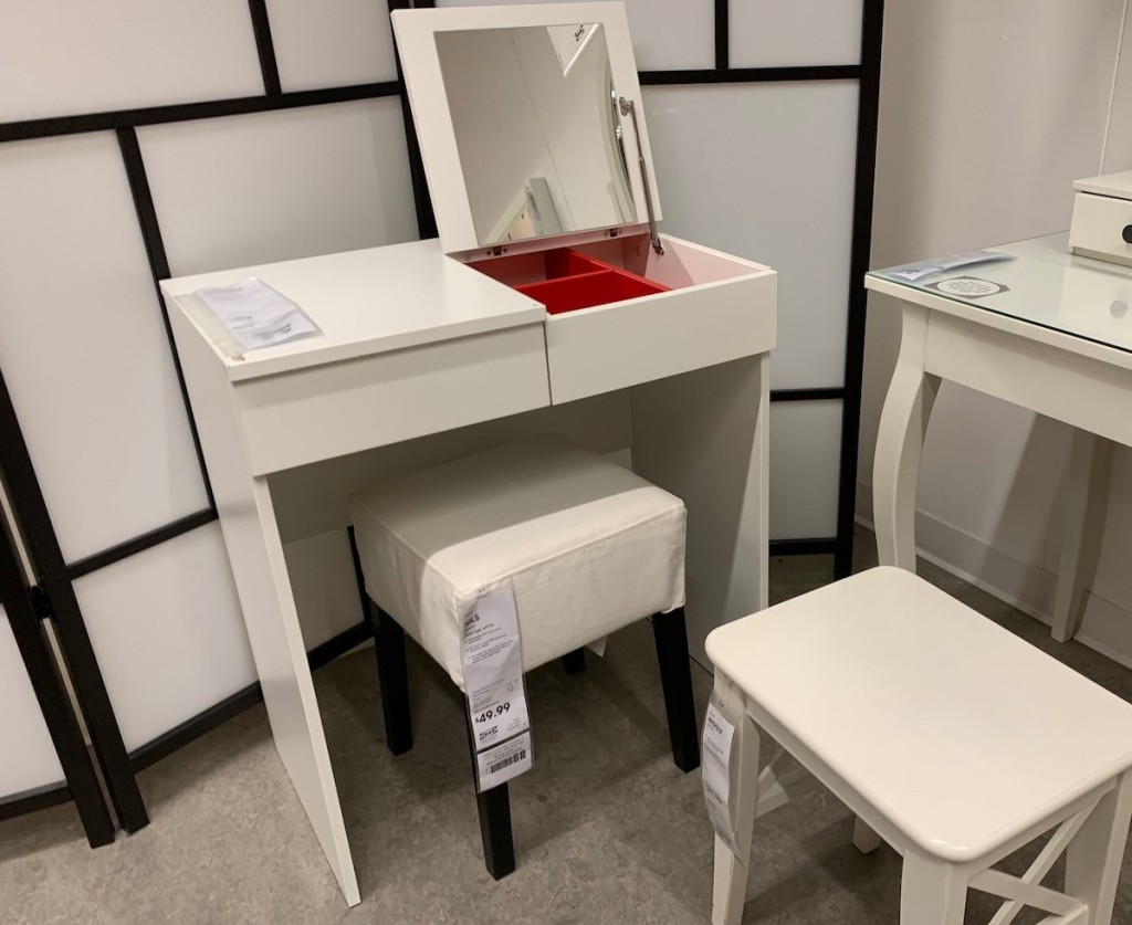 small white makeup vanity with open lid and white stools