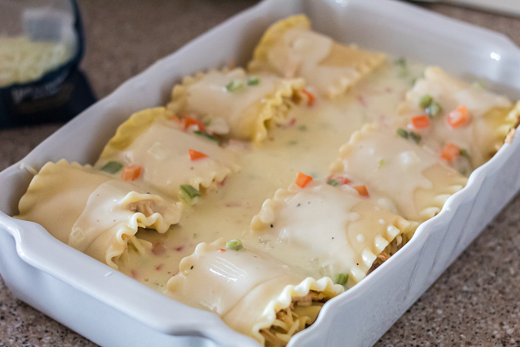spicy chicken lasagna roll-ups with creamy sauce in casserole dish