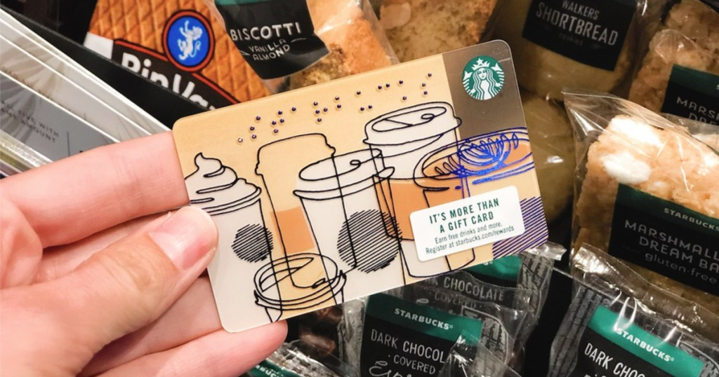 woman hand holding starbucks gift card with coffee images on the card
