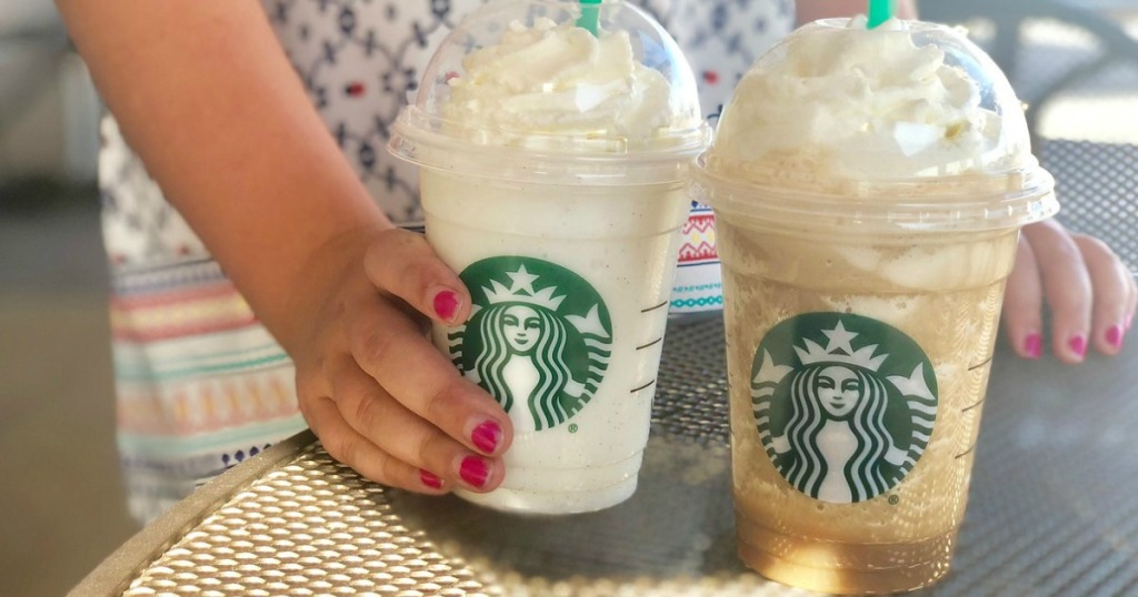hand holding coffee drink by table