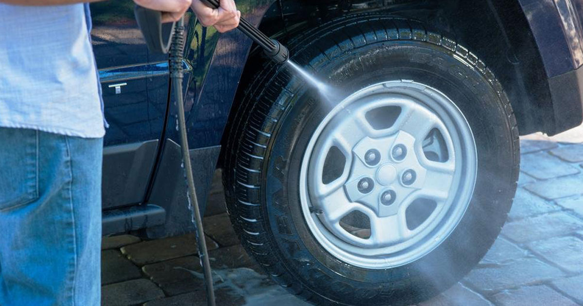 guy pressure washing tire of car with armor all pressure washer at home depot