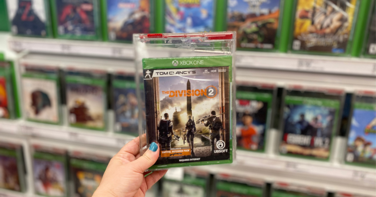 hand holding up tom clancy's the division 2 video game with blurred background