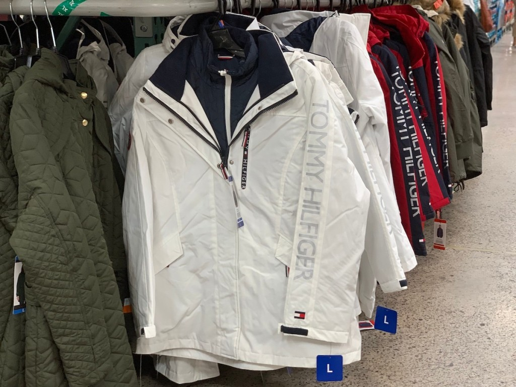 row of tommy hilfiger winter coats hanging on rack